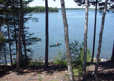 A view of a kayaker, seen from log cabin